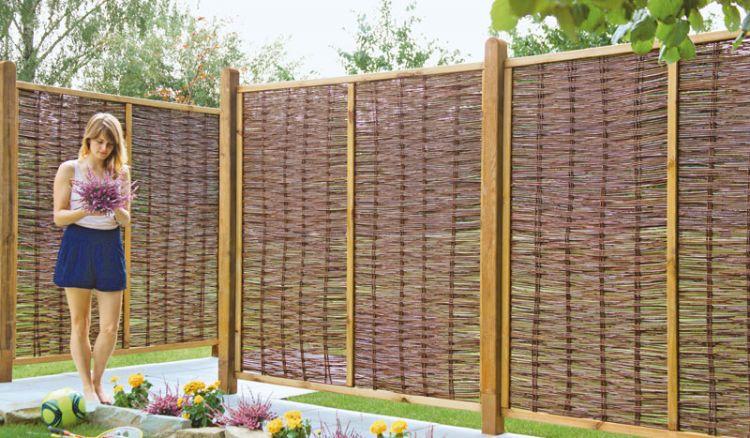 Der Sichtschutzzaun aus geölter Weide mit einem Rahmen aus braun gebeiztem Kiefernholz ist ein natürlicher Sichtschutz für alle Gartenliebhaber, die eine naturverbundene Optik zu schätzen wissen.