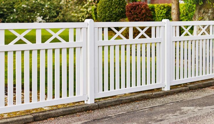 Der weiße Gartenzaun ist mit rostfreien Nägeln und Schlagschrauben verarbeitet, die Tore sind durch diagonale Latten und Stahl verstärkt