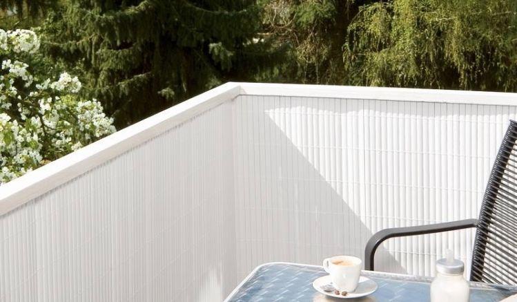 Balkonsichtschutz mithilfe einer weißen PVC-Sichtschutzmatte.