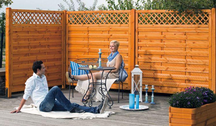 Die Sichtschutzwand aus gehobeltem,  kesseldruckimprägniertem und in Pinie lasiertem Kiefernholz ist in 3 Ausführungen erhältlich: 180 x 180 cm, 90 x 180 cm und 90 x 180 auf 90 cm