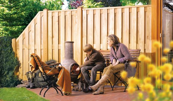 """Der Sichtschutzzaun """"Newa"""" aus naturbelassener Sibirischer Lärche fügt sich durch den warmen Farbton des Holzes harmonisch in jeden Gartenbereich ein."""
